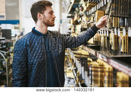 Bearded young man in a hardware store standing reading the information on a product hanging on the rack side view close up