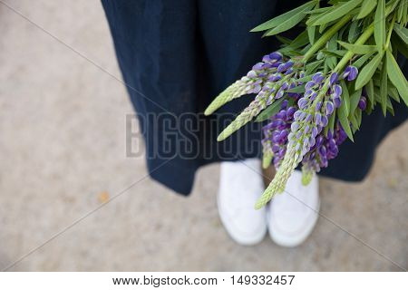 Closeup of woman's hands holding blue flowers lupine outdoors. Woman with wild flowers bouquet walking in the park.