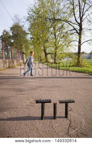 kid boy playing skittles in the street. Russian game skittles. Wooden skittles. Outdoor activites with children. Child playing in the sun.