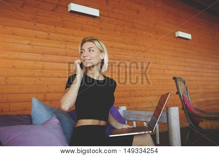 Young woman is smiling for friends during talk via smart phone while is sitting in modern co-working space.Beautiful hipster girl is calling via cell telephone during work on portable laptop computer