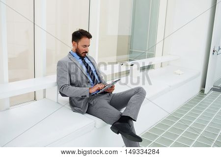 Man financier is reading financial news in network via portable touch pad while is sitting in modern office interior. Male specialist in the legal profession is using digital tablet before interview