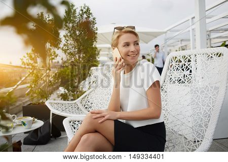 Cheerful female entrepreneur having pleasant mobile phone conversation during lunch break in restaurant. Happy woman is smiling foe someone while is talking on cell telephone during rest in cafe