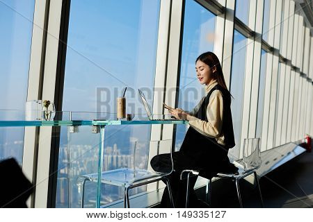 Confident Chinese woman managing director is reading e-mail on cell telephone while is waiting reboot her portable laptop computer while is sitting in loft with contemporary interior and big window