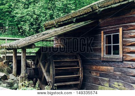 Old wooden waterwheel watermill. The old water wheel covered with moss. Flowing water to the mill. Old technology energy water movement