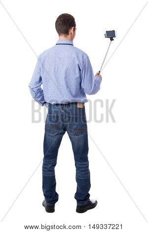 Back View Of Business Man Taking Selfie Photo With Smart Phone On Selfie Stick Isolated On White