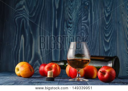 Glass With Calvados Brandy And Yellow Apples On A Wooden Table