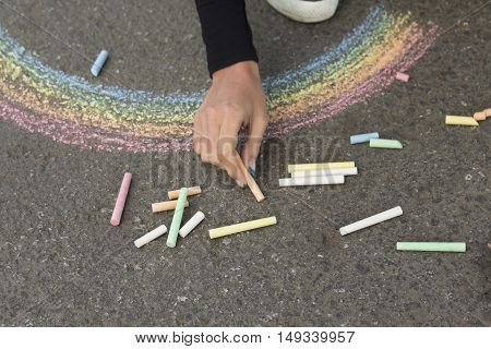 Hand draws with crayons colored Rainbow girl on the pavement