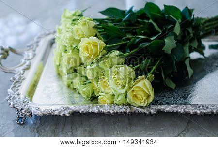 Yellow green roses/ beautiful bouquet on a silver antique tray on stone background
