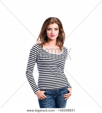 Beautiful young woman in jeans and striped long sleeved t-shirt, studio shot on white background, isolated