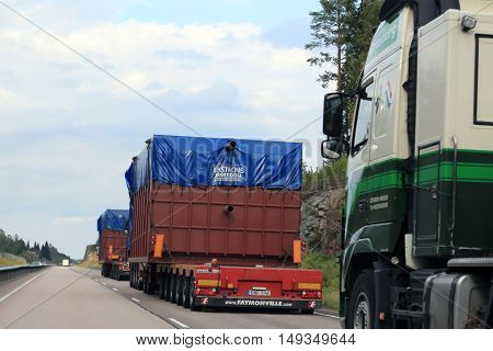 ORIVESI FINLAND - SEPTEMBER 1 2016: Convoy of semi trucks transport industrial objects as oversize loads uphill along road. Rear view of the transports as seen from the moving car overtaking the vehicles.