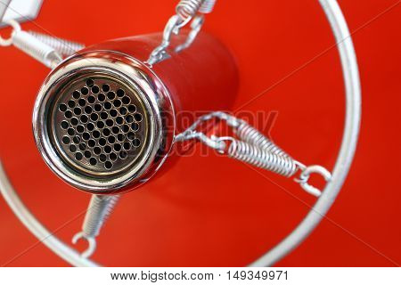 Vintage retro style old metal professional studio vocal voice and music recording microphone suspended with spiral round frame close up over red background