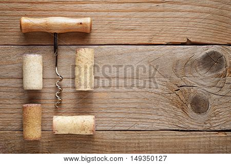 Corkscrew and wine corks on wooden background top view