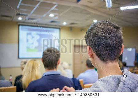 Education, High School, Teamwork And People Concept -  Students Sitting In Lecture Hall From Back