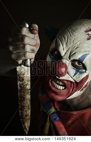 a scary evil clown with a big knife in his hand, against a dark background