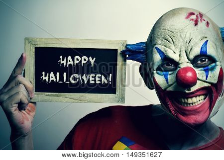 portrait of a scary evil clown with a chalkboard with the text happy Halloween written in it