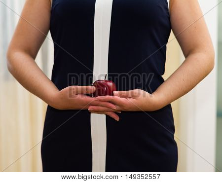 Closeup womans stomach wearing blue dress, holding apple between hands, weightloss concept.