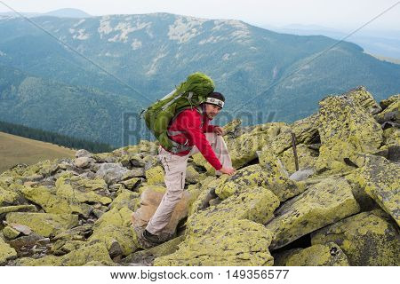 Happy hiker climbs the mountain winning reaching life goal success freedom and happiness achievement in mountains. Hiker with backpack on top of a mountain.Concept of success