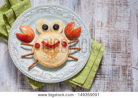 Funny breakfast for child. Pancake crab with apple.