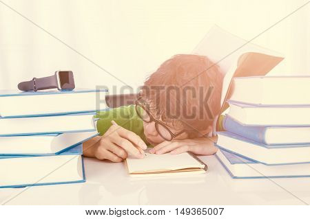Discouraged student sleep on table in front of his homework