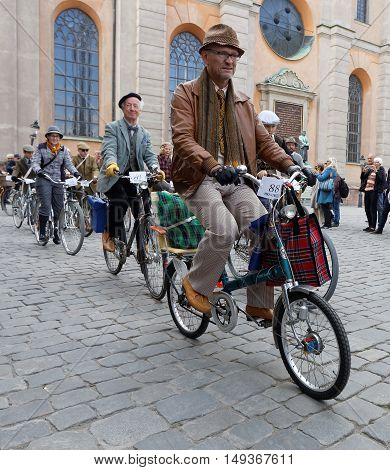 STOCKHOLM - SEPT 24 2016: Man cycling on a mini bicycle dressed in old fashioned clothes in the Bike in tweed event September 24 2016 in Stockholm Sweden