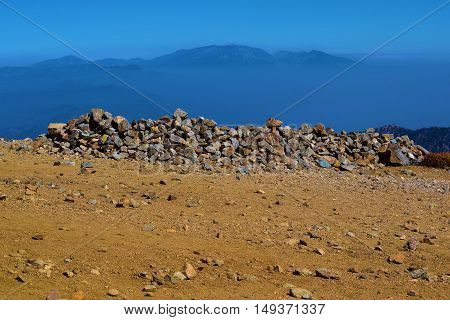 Pile of rocks which is a landmark indicating the summit of Mt Baldy which is over 10,000 feet in elevation overlooking the Southern California landscape