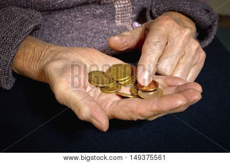 Euro coins in old woman's hands. Bussines concept.