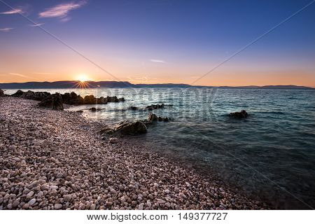 Sunrise with the red sky and clear turquoise ocean over the beach and Adriatic sea in Croatia Istria Europe