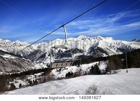 Ski Slope And Chair-lift In Snow Winter Mountains At Sun Windy Day