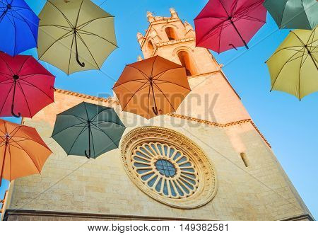 Colorful Umbrellas Against Gothic Cathedral And Blue Sky.