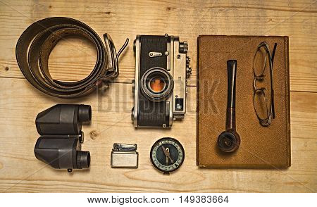 Still life with retro object. Book with compact old camera compass cigarette lighter belt glasses pipe binocular on wood table.