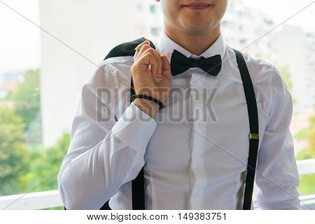 Fashion detail of groom wearing bowtie. Final preparations for wedding.