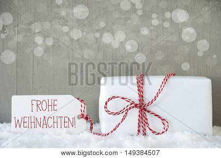 One Christmas Present On Snow. Cement Wall As Background With Bokeh. Modern And Urban Style. Card For Birthday Or Seasons Greetings. Label With German Text Frohe Weihnachten Means Merry Christmas