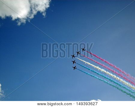 Royal Air Force Red Arrows aerobatic display team in flight with red blue and white smoke. Five aircraft. Background of blue sky with white clouds.