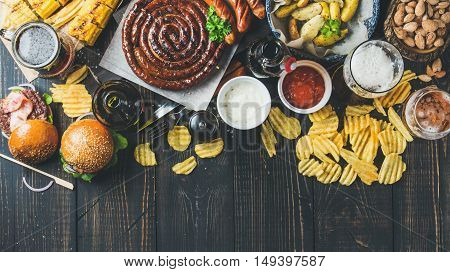 Beer and snack set. Octoberfest food frame concept. Variety of beers, grilled sausages, burgers, corn, fried potatoes, chips, salted almonds and sauces on dark wooden background. Top view, copy space