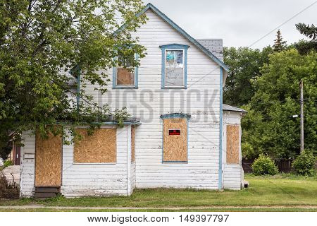 horizontal image of an old condemned house with windows boarded up and