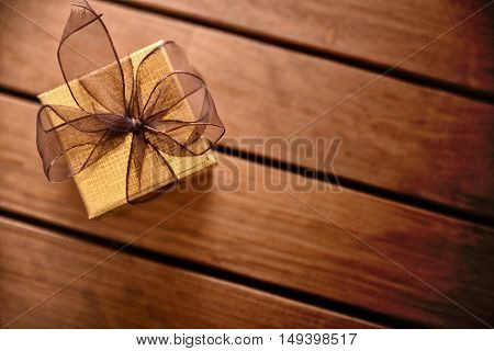 Golden Gift Box On Diagonal Table Wooden Slats Top View