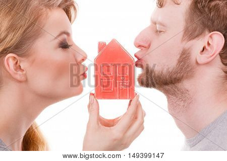 Housing family love romance future concept. Couple share kisses with house symbol. Young married man lady blow kiss with home model.
