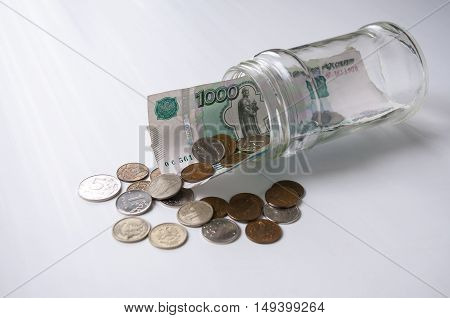 A thousand rubles and fines sticking out of a glass jar lying