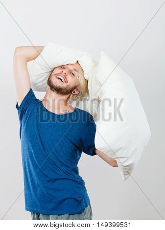 Sleeping well concept. Happy young man rested after good night sleep playing with downy cushion laughing and having fun