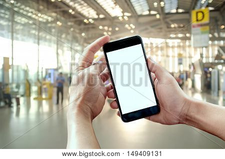 Smart phone showing blank screen in man hand at Check in Counter and Passengers in a airport departure terminal.