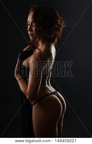Erotica. Sensual pretty woman posing in studio, on gray background