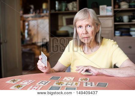 Woman Holding Playing Card At Table