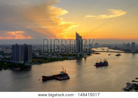 Beautiful evening sunset of Chao Phraya River, Many cargo ships docked in the middle river near the Rama 9 Bridge, among many passenger ship sailed through.