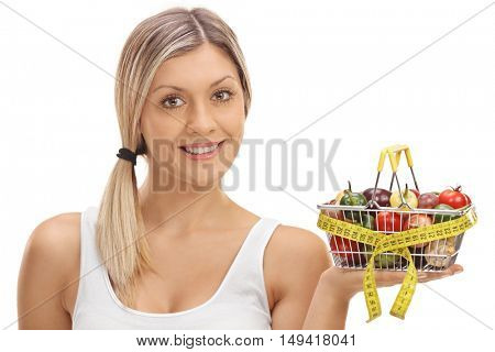 Joyful woman holding a small shopping basket full of fruits and vegetables wrapped with measuring tape isolated on white background