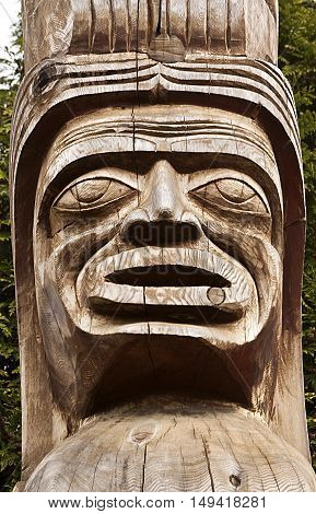 Vertical close up of carved wood Totem Pole face in Stanley Park. They are located on the eastern point, just before Hallelujah Point on a bright, sunny spring day.