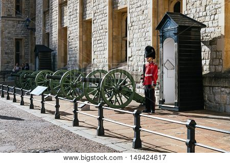 LONDON UK - AUGUST 21 2015: Queen's Guard and guns - Tower of London. The Queen's Guard is the contingents of infantry and cavalry soldiers charged with guarding the official royal residences in the United Kingdom.