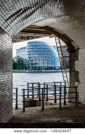 LONDON UK - AUGUST 21 2015: London City Hall framed by the archs of Tower Bridge. The City Hall was designed by Norman Foster.