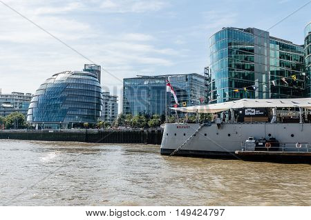 LONDON UK - AUGUST 22 2015: London City Hall and HMS Belfast battleship from the river a sunny day.