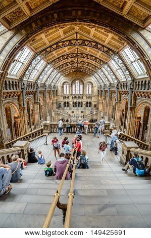 London UK - August 19 2015: Tourists sitting on stairs in the Main hall of famous London Natural History Museum. High angle view with a wide open lens