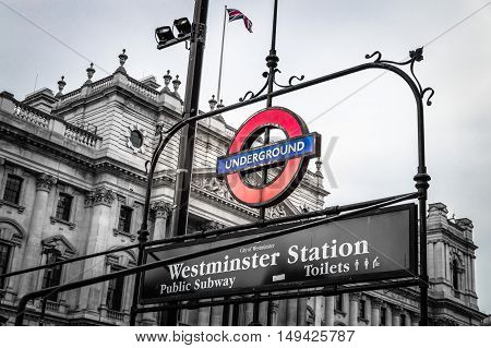 London UK - August 18 2015: London underground sign of Westminster station. The London Underground logo is one of the most recognised British icons. Black and white image with color sign